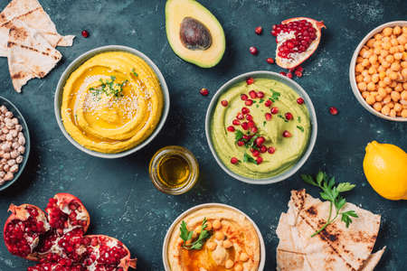 Bowls with yellow hummus and green hummus, tahini, olive oil, sesame seeds, pita, raw chickpeas, avocado, pomegranate on dark background. Middle eastern, jewish, arabic cuisine. Top view Stockfoto