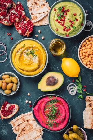 Ingredients for yellow turmeric hummus, green parsley hummus and red beetroot hummus on dark background, lemon, sesame, olive oil, pita, avocado, pomegranate. Middle eastern, jewish, arabic cuisine.