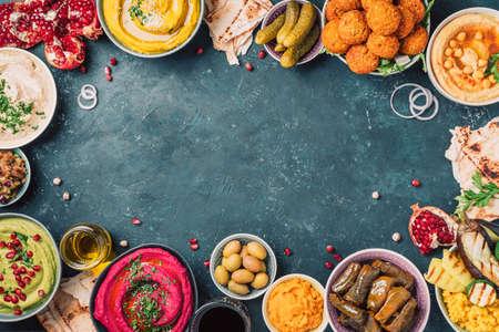 Traditional Middle Eastern assorted meze: hummus, pita, olives, pistachios, dolma, falafel balls, pickles, babaganush, vegetables, pomegranate, eggplants. Top view. Banner. Copy space. Arab meal Foto de archivo