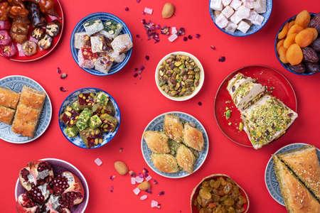 Traditional turkish delight on red background. Top view. Flat lay. Copy space. Arab dessert, baklava, halva, rahat lokum, sherbet, nuts, pistachios, dates, raisins, dried apricots, churchkhela. Stock Photo