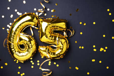 Gold foil balloon number, digit sixty-five. Birthday greeting card with inscription 65. Anniversary celebration event. Banner. Golden numeral, black background. Numerical digit, light bokeh, glitter