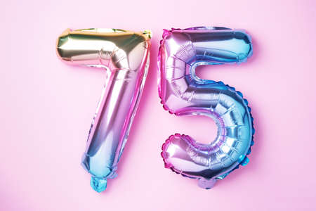 Rainbow foil balloon number, digit seventy-five. Birthday greeting card with inscription 75. Anniversary concept. Top view. Colored numeral on pink background. Numerical digit, Celebration event