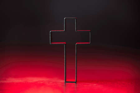 Christian cross on red background with soft bokeh lights background. Copy space. Banner. Church worship, salvation concept. Faith symbol in Jesus Christ. Holy cross for good friday, Easter day