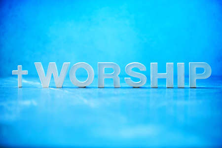 Word Worship made with cement letters on blue marble background. Copy space. Biblical, spiritual or christian reminder. Good friday, Easter day in church. Christian music concert, Sunday service
