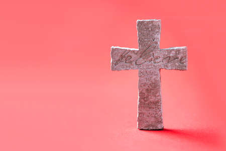 Stone cross with inscription Believe on red background, Copy space. Christian backdrop. Biblical faith, gospel, salvation concept