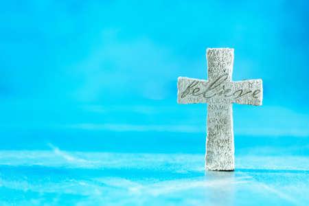 Stone cross with inscription Believe on blue background, Copy space. Christian backdrop. Biblical faith, gospel, salvation concept. Banner