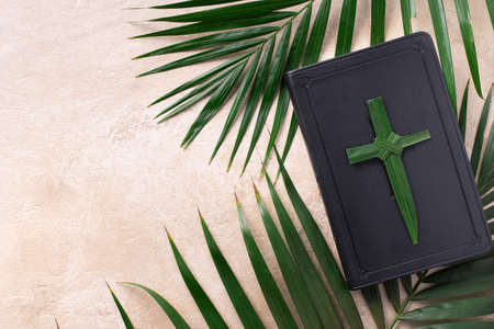 Palm Sunday concept. Palm cross on open Holy Bible and palm leaves. Reminder of Jesus sacrifice and Christ resurrection. Easter passover. Eucharist concept. Christianity symbol and faith Foto de archivo