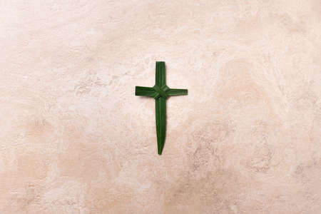 Palm Sunday concept. Cross made of palm and tropical leaves. Christian moveable feast to celebrate Jesus triumphal entrance into Jerusalem