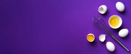 Eggs in white bowl with whisk on violet background. Baking frame. Banner Stockfoto