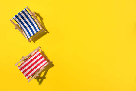 Two deck chairs with hard shadow, monstera and palm leaves on yellow paper background. Flat lay and copy space. Summer travel vacation concept. Minimal composition