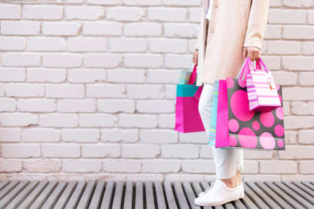 Shopping concept. Girl holding bunch of shopping bags with purchases near brick background. Copy space. Sale, discount, black friday concept. Shopping mall and outlet
