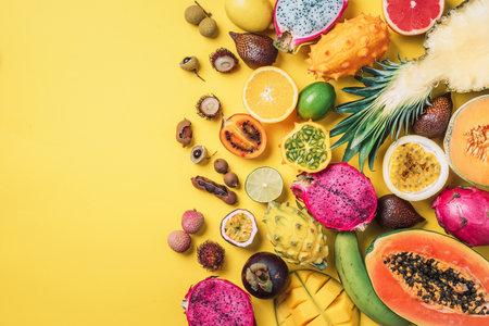 Exotic fruits - pineapple, papaya, mango, annona, banana, pitahaya, kiwano, african horned melon, tamarillo fruit, granadilla, salak, snake fruit, maracuya, rambutan, lychee, longan, tamarind, mangosteen on yellow background. Tropical fruits concept. Top view. Copy space