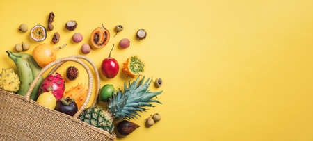 Exotic fruits in straw summer bag on yellow background. Top view. Copy space. Tropical fruits flat lay. Zero waste, plastic free concept. Travel and holiday concept. Vegan, vegetarian healthy diet. Banner Stockfoto