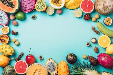 Tropical fruits concept. Exotic fruits - pineapple, papaya, mango, annona, banana, pitahaya, kiwano, african horned melon, tamarillo fruit, granadilla, salak, snake fruit, maracuya, rambutan, lychee, longan, tamarind, mangosteen on blue background. Top view. Copy space