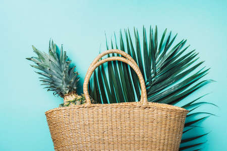 Pineapple in straw bag on wooden background. Top view. Copy space. Summer travel concept. Sustainable lifestyle. Zero waste, plastic free concept. Stockfoto