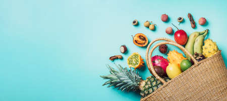 Exotic fruits in straw summer bag on blue background. Top view. Copy space. Tropical fruits flat lay. Zero waste, plastic free concept. Travel and holiday concept. Vegan, vegetarian healthy diet. Banner