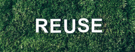 Word Reuse on moss, green grass background. Top view. Copy space. Banner. Biophilia concept. Nature backdrop