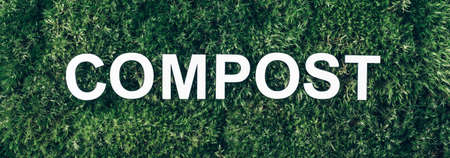 Word Compost on moss, green grass background. Top view. Banner. Biophilia concept. Reduce food waste. Organic waste, composting waste for recycling. Environmentally responsible behavior concept