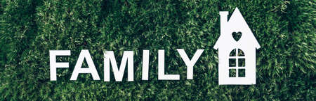 Family concept. White home icon, inscription family on green grass field, moss background. Top view. Copy space. Banner. Biophilia concept. Nature concept, eco friendly lifestyle
