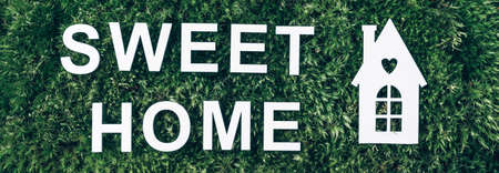 Home sweet home concept. White house and inscription icon on green grass field, moss background. Top view. Copy space. Banner. Biophilia concept. Nature concept, eco friendly lifestyle