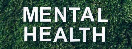 Inscription Mental health on moss, green grass background. Top view. Copy space. Banner. Biophilia concept. Nature backdrop Stockfoto