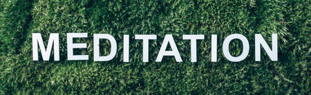 Word Meditation on moss, green grass background. Top view. Copy space. Banner. Biophilia trend. Nature backdrop. Peace of Mind, health concept Stockfoto