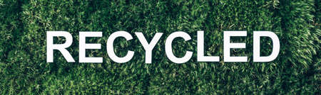 Word Recycled on moss, green grass background. Top view. Copy space. Banner. Biophilia concept. Nature backdrop