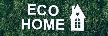 White eco house model on green grass, inscription Eco home over moss backdrop. Top view. Copy space. Banner. Biophilia concept. Nature concept, eco friendly lifestyle Stockfoto
