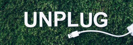 Word Unplug, white internet usb adapter on moss, green grass background. Top view. Copy space. Banner. Biophilia concept. Nature backdrop