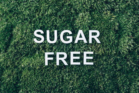 Inscription Sugar Free on moss, green grass background. Top view. Copy space. Banner. Biophilia concept. Nature backdrop. Healthy diet