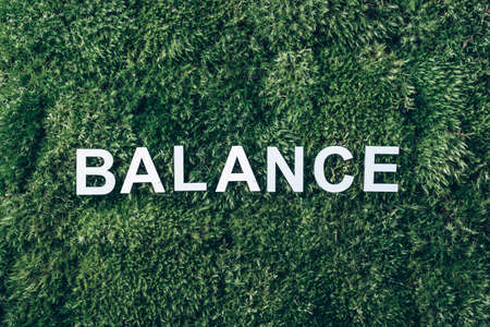 Word Balance on moss, green grass background. Top view. Copy space. Banner. Biophilia trend. Nature backdrop. Work Life Balance. Business work life concept. Body, soul, mind 版權商用圖片
