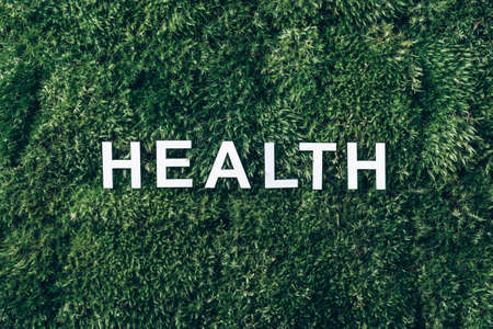 Word Health on moss, green grass background. Top view. Copy space. Banner. Biophilia trend. Nature backdrop. Mental Health concept