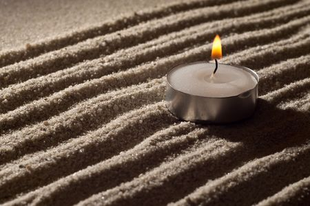 Lit Tea Candle on White Sand in Abstract Lighting photo