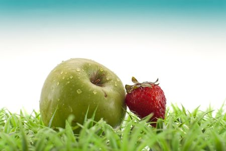 drenched: Water Drenched Strawberry and Apple on Grass