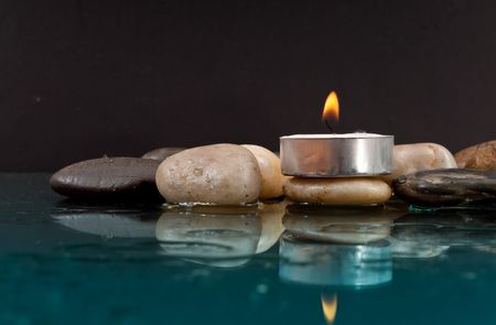 Peaceful Setting with Rocks and Candle on Water photo