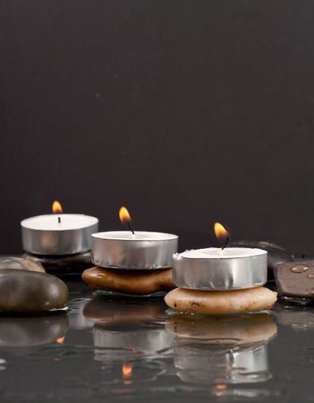 Tea Candle Lit on Top of Rocks in Water photo