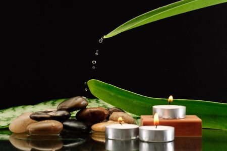elemental: Falling Water Drops Coming From Leaf Onto Stones and Candles Stock Photo