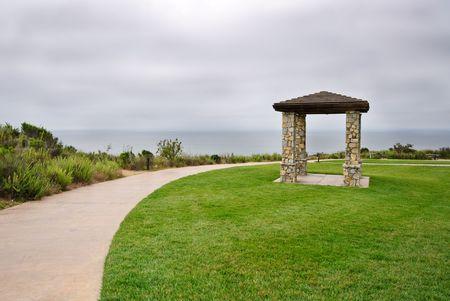curvature: Stone Pillared Gazebo in Grass Near Curvature of Walkway