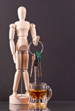 Wooden Dummy Holding Keys Above a Shot of Whiskey photo