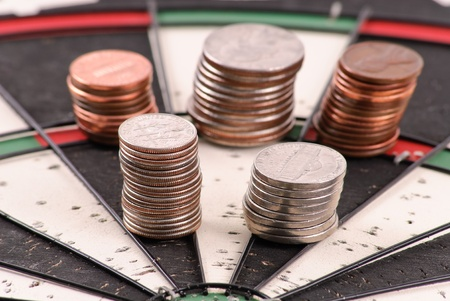 Dime and Nickel Stack on Dart Board for Financial Goals Concept Stock Photo