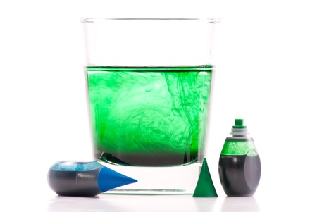 blue green background: Green Food Coloring Swirling in Glass of Water Stock Photo