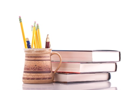 thesis: Cup of Pens and Pencils with College Textbooks Stock Photo