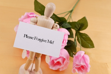 forgive: Wood Doll Holding Up an Apology Note