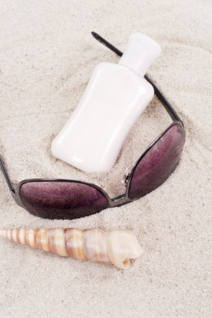 Sun Block with Sunglasses and Shell on the Sand photo