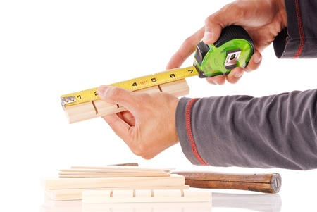 Hands Measuring a Piece of Pine Wood Stock Photo - 9468826