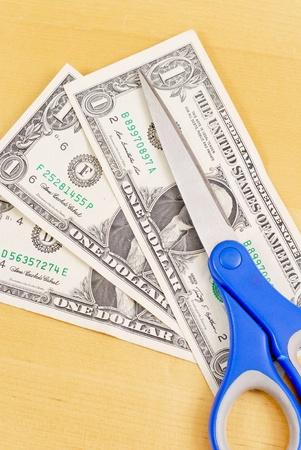 deficient: Scissors on Dollar Bills for Budge Cut Concept Stock Photo