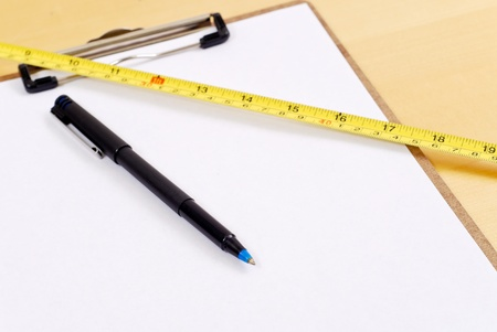 Pen on Clipboard with Construction Tape Measure photo