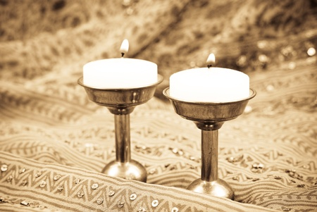 Lit Tea Candles on Bronze Stands in Sepia photo