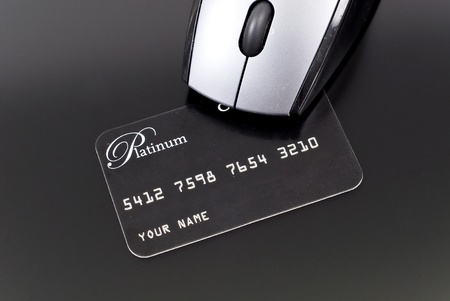Platinum Credit Card Under the Front of Computer Mouse photo