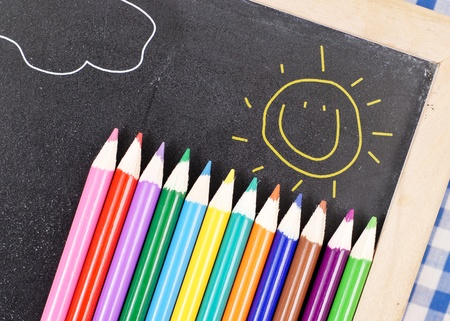 Colored Pencils on Chalk Board with Happy Sun Drawing photo